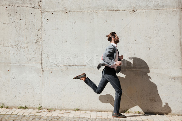 Full length portrait of a young man in jacket running Stock photo © deandrobot