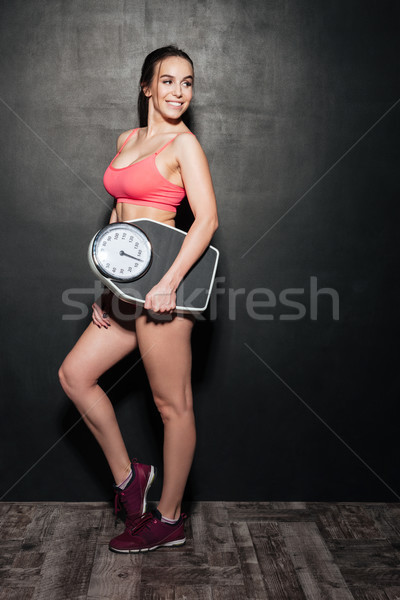 Cheerful woman holding weigher isolated Stock photo © deandrobot