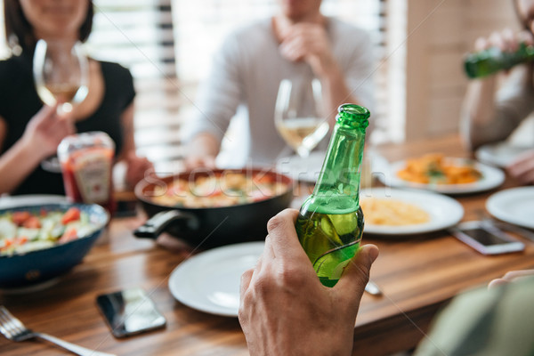Man with bottle of beer sitting and celebrating with friends Stock photo © deandrobot