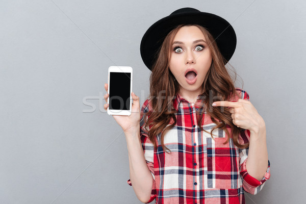 Portrait of a shocked girl in plaid shirt pointing finger Stock photo © deandrobot