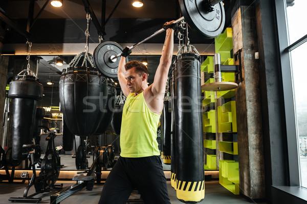 Serious sportsman make sport exercises in gym Stock photo © deandrobot