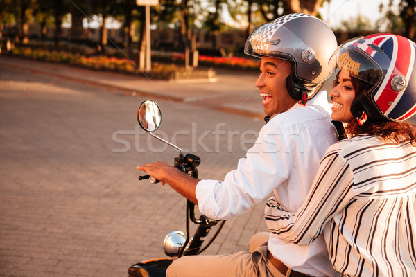 Side view of joyful african couple rides on modern motorbike Stock photo © deandrobot