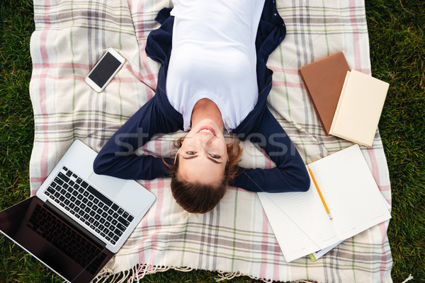 Top view of a smiling young student girl resting Stock photo © deandrobot