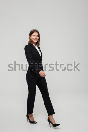 Full length portrait of a smiling beautiful woman in suit Stock photo © deandrobot