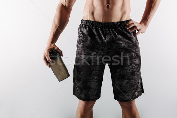 Cropped image of strong young sportsman holding bottle of water. Stock photo © deandrobot