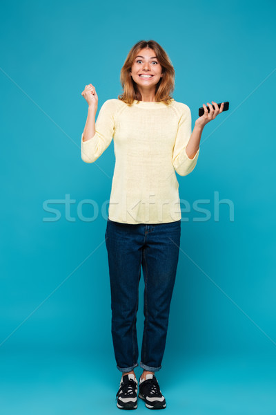Full length image of Happy woman in sweater rejoice Stock photo © deandrobot