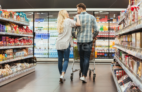 Back view of a smiling couple walking with a trolley Stock photo © deandrobot