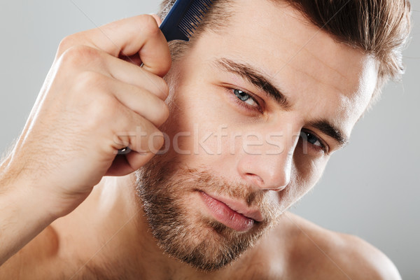 Close up portrait of a handsome man combing his hair Stock photo © deandrobot