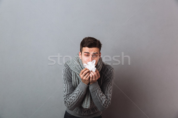Displeased illness man wearing warm scarf holding napkin. Stock photo © deandrobot
