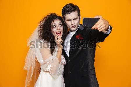 Picture of Funny punk couple posing and looking at camera Stock photo © deandrobot