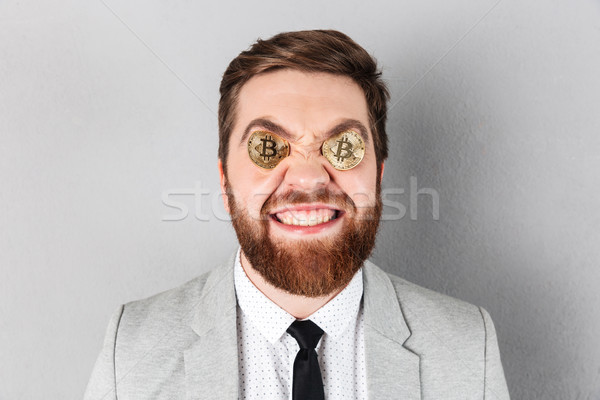 Close up of a cheerful businessman with bitcoins Stock photo © deandrobot