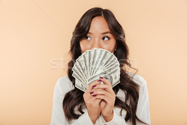 Portrait of successful asian woman covering mouth with fan of 10 Stock photo © deandrobot