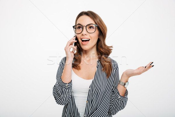 Portrait of a cheery casual girl talking on mobile phone Stock photo © deandrobot