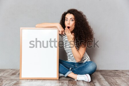 Caucasian woman with beautiful hair posing with legs crossed dem Stock photo © deandrobot