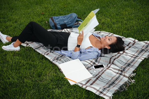 Young cheerful asian female student reading book, lying on the g Stock photo © deandrobot