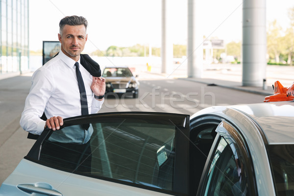 Smiling mature businessman getting in taxi outside Stock photo © deandrobot