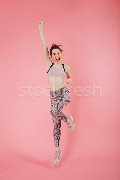 Full length image of Joyful sportswoman rejoices Stock photo © deandrobot