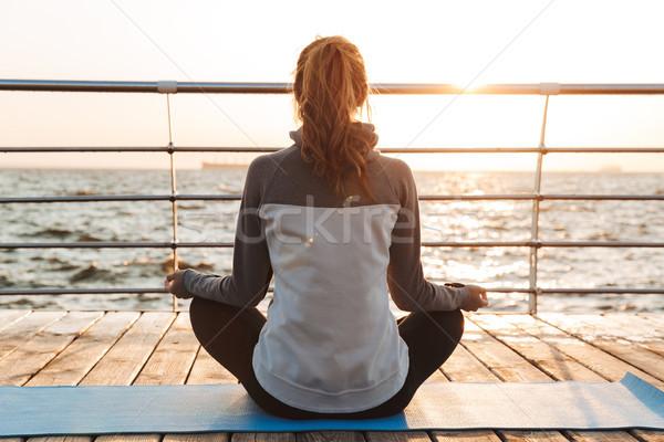 Hátulnézet fiatal lány meditál ül fitnessz víz Stock fotó © deandrobot