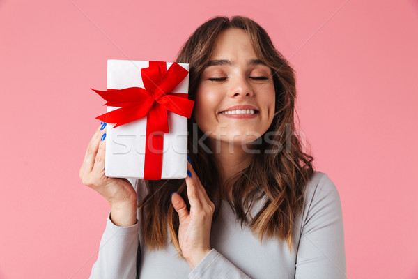 Cute pleased young pretty woman holding surprise gift present box. Stock photo © deandrobot