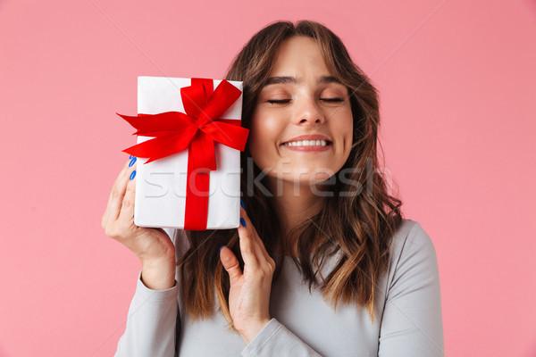 Aranyos elégedett fiatal csinos nő tart meglepetés Stock fotó © deandrobot