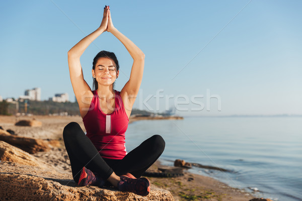 Satisfied young sportswoman sitting in yoga position Stock photo © deandrobot