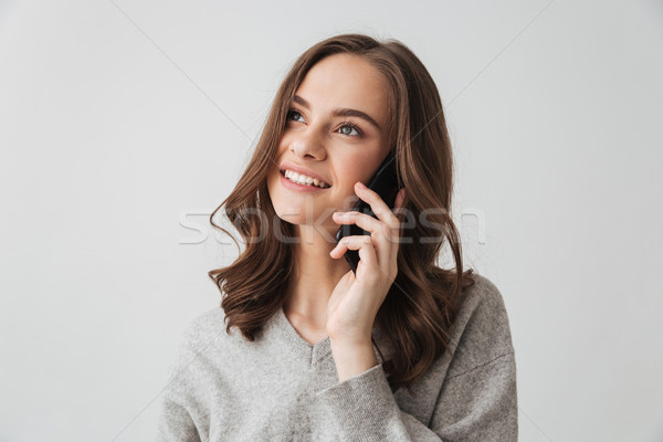 Smiling brunette woman in sweater talking by smartphone Stock photo © deandrobot