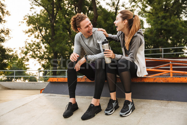 Image of happy sporty couple man and woman 20s in tracksuits, la Stock photo © deandrobot