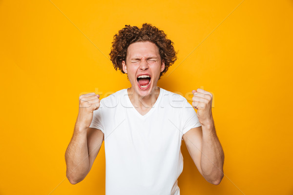 Portrait of a happy curly haired man screaming Stock photo © deandrobot