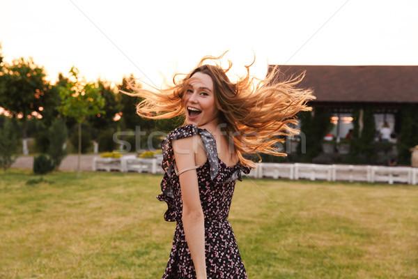 Foto jonge blijde vrouw glimlachen lopen outdoor Stockfoto © deandrobot