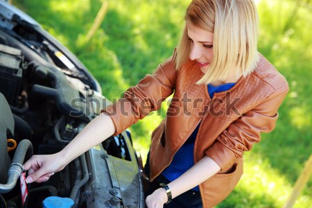 Blonde woman checking her car engine Stock photo © deandrobot
