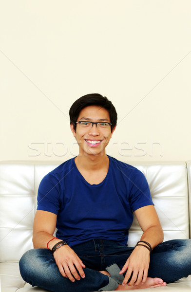 Stock photo: Asian man relaxing at home sitting on sofa