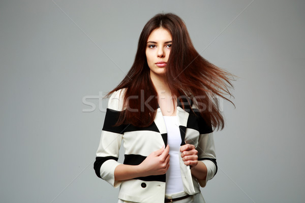 Studio shot of a young beautiful woman in casual clothes on gray background Stock photo © deandrobot