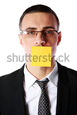 Portrait of businessman with mouth covered with a paper card over white background Stock photo © deandrobot