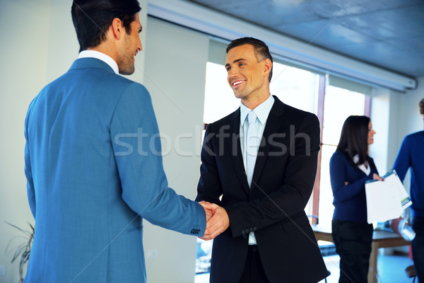 Two happy businessman handshaking in conference hall Stock photo © deandrobot