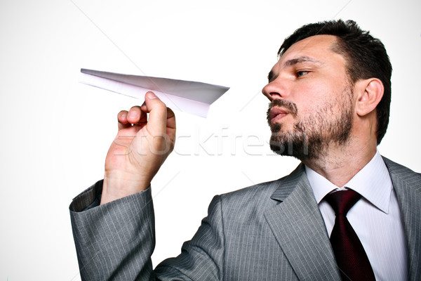 A business man throwing a paper plane Stock photo © deandrobot