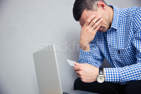 Upset man holding credit card Stock photo © deandrobot