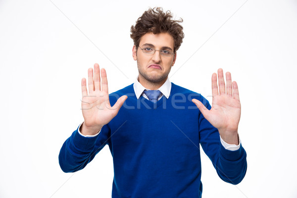 Handsome man showing stop gesture over white background Stock photo © deandrobot
