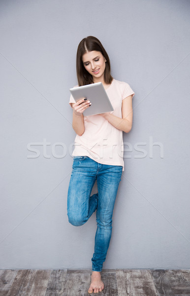 Young woman using tablet computer and leaning on the gray wall Stock photo © deandrobot