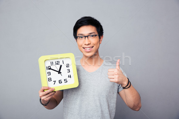 Happy asian man holding big clock and showing thumb up Stock photo © deandrobot