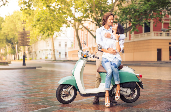 Happy beautiful couple on scooter in old european city Stock photo © deandrobot
