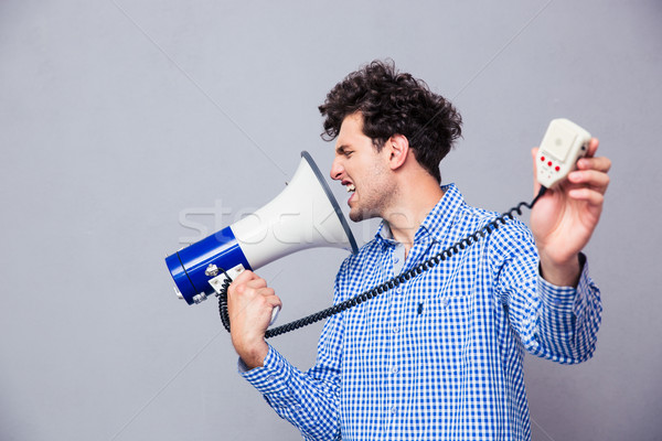 Man directing megaphone at herself Stock photo © deandrobot