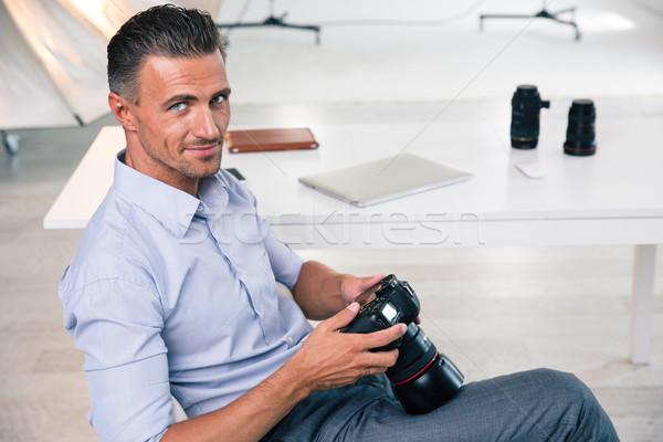 Smiling handsome photographer using camera Stock photo © deandrobot