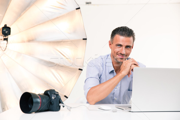 Smiling photographer using laptop Stock photo © deandrobot
