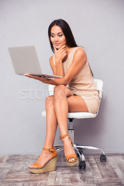 Woman sitting on office chair with laptop Stock photo © deandrobot