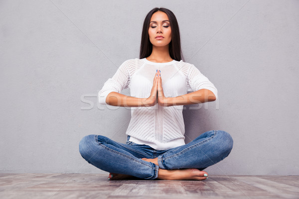 Woman in jeans meditating on the floor Stock photo © deandrobot