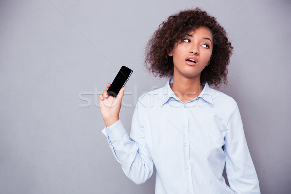 Bored afro american woman holding smartphone Stock photo © deandrobot