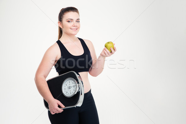 Fat woman holding weighing machine and apple  Stock photo © deandrobot