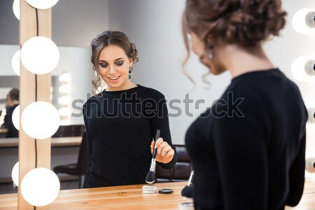 Woman looking at her reflection in the mirror  Stock photo © deandrobot