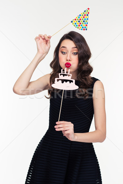 Curly woman blowing on fake birthday cake with candles props  Stock photo © deandrobot