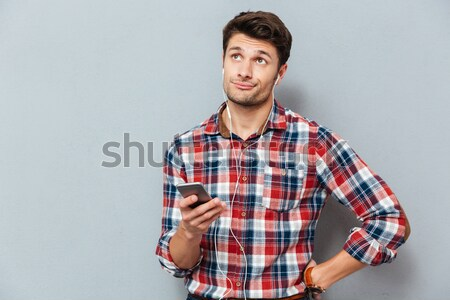 Poor handsome young man in checkered shirt showing empty pockets  Stock photo © deandrobot